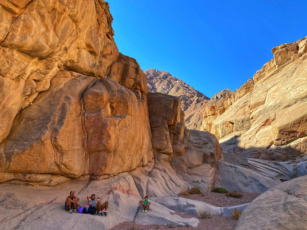 people climbing rocky mountain during daytime