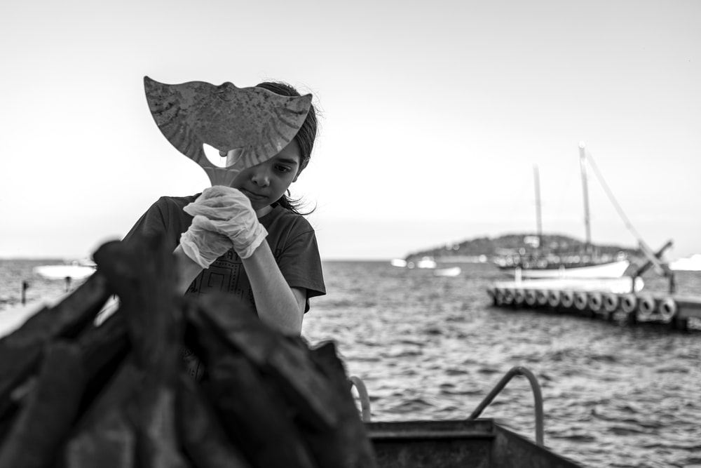 grayscale photo of woman in white shirt and hat sitting on boat