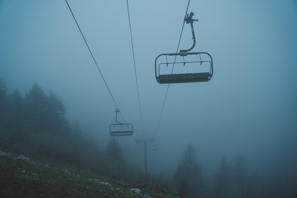 black cable car over green trees during daytime