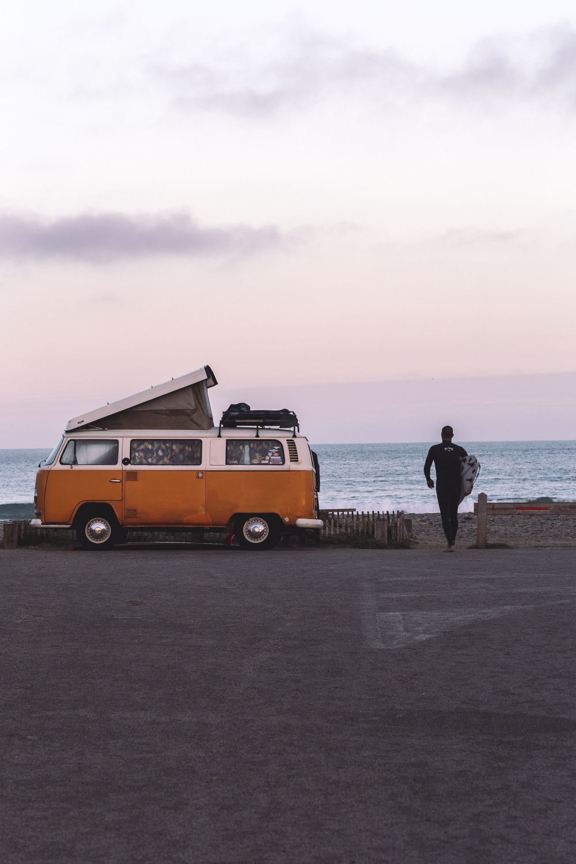 man in black jacket standing on beach during daytime