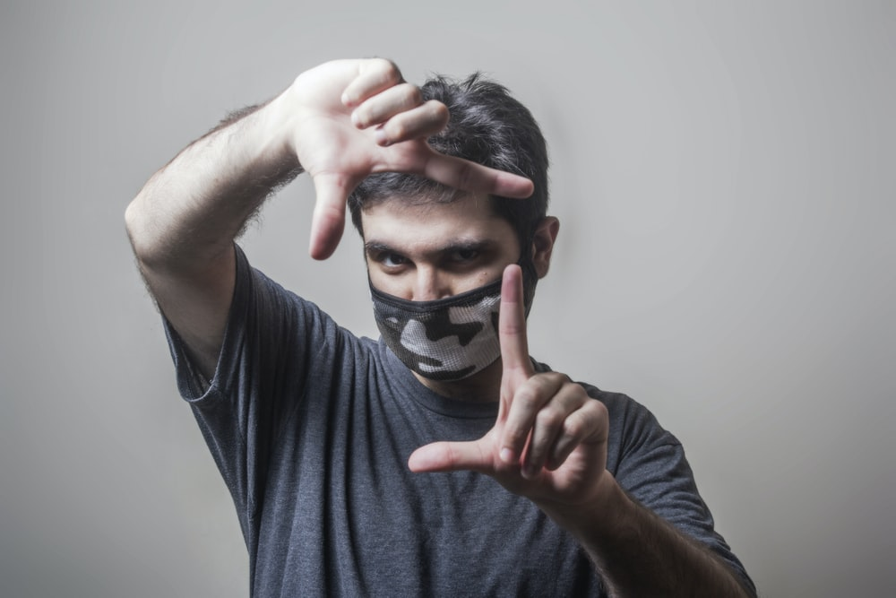 man in black crew neck t-shirt covering his face with his hand