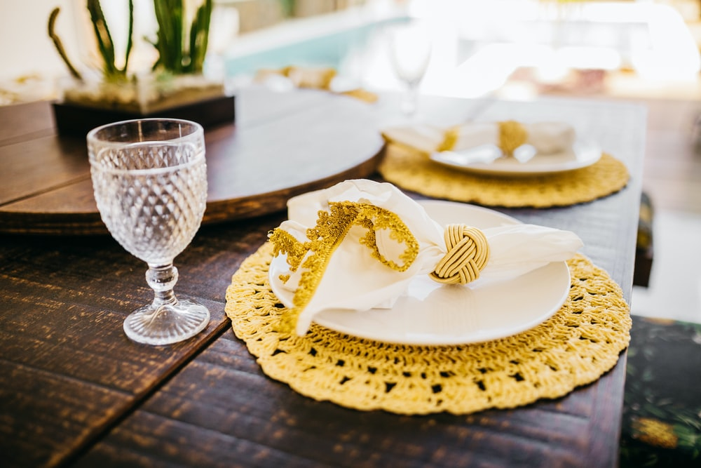 white and gold round plate on brown wooden table