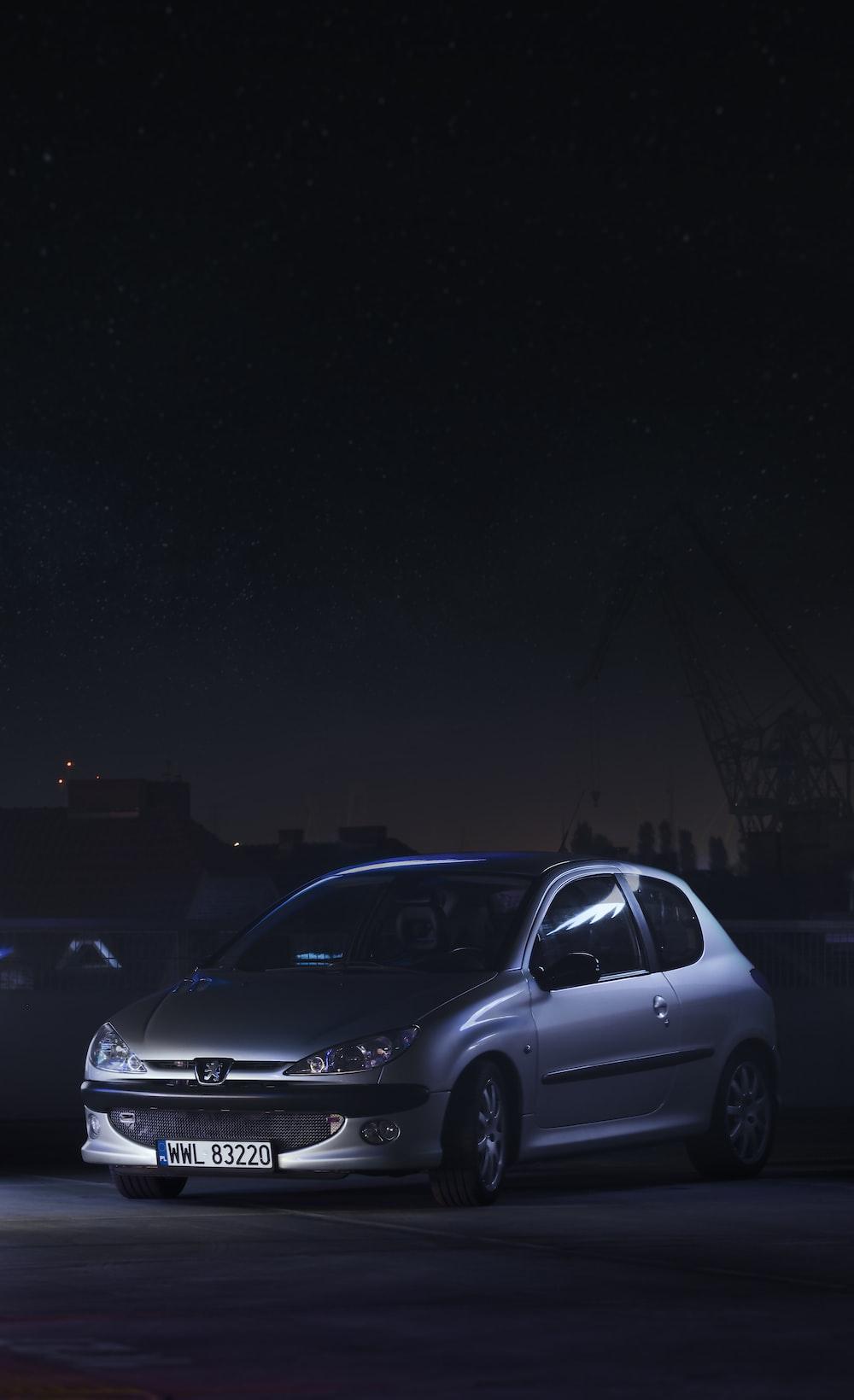 silver sedan on road during night time
