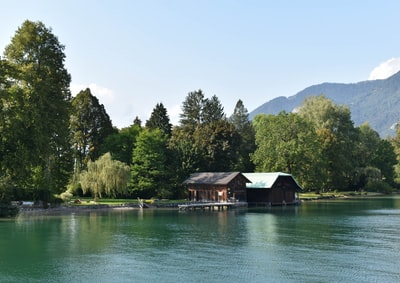 brown wooden house on lake near green trees during daytime österreich zoom background