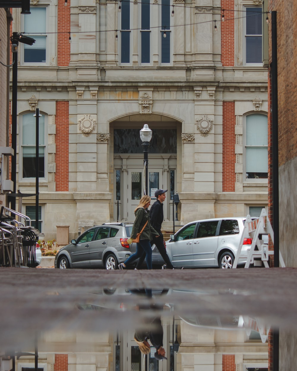 man in black jacket walking on sidewalk near cars parked beside brown building during daytime