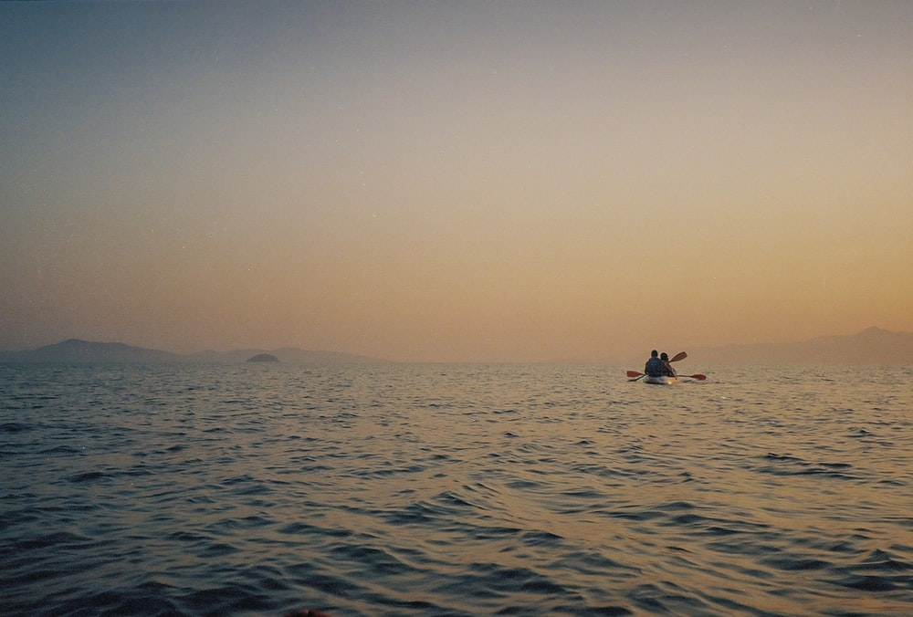 2 people in the middle of the sea during daytime