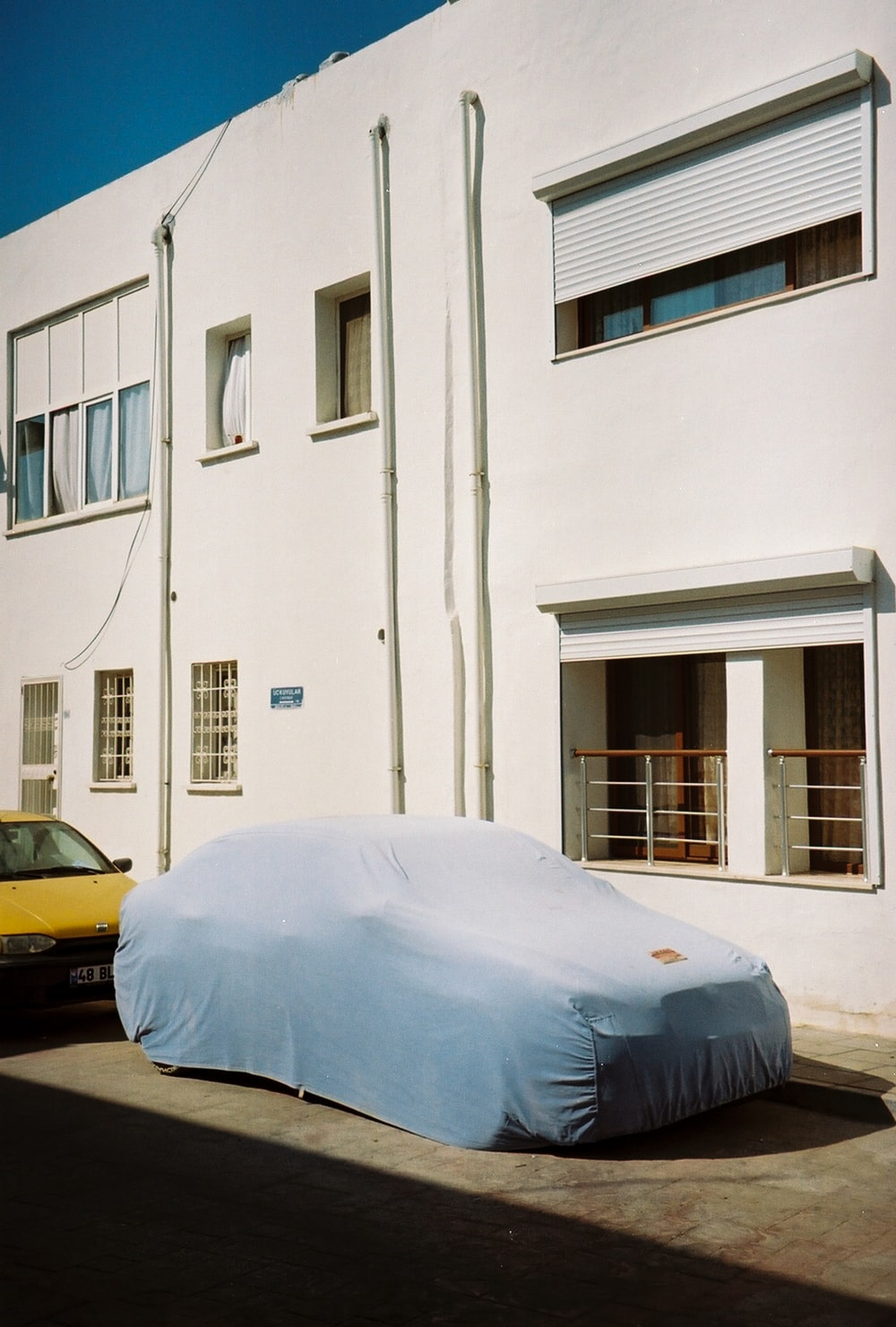 yellow car parked beside white concrete building during daytime