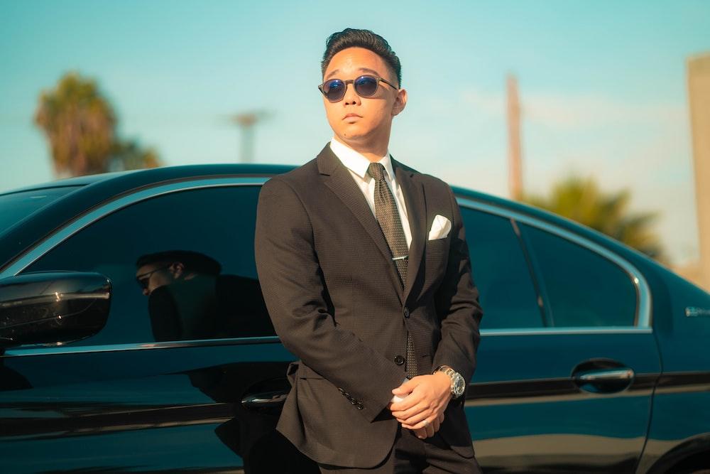 man in black suit standing beside black car during daytime