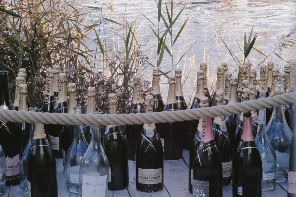 black glass bottles on brown wooden fence