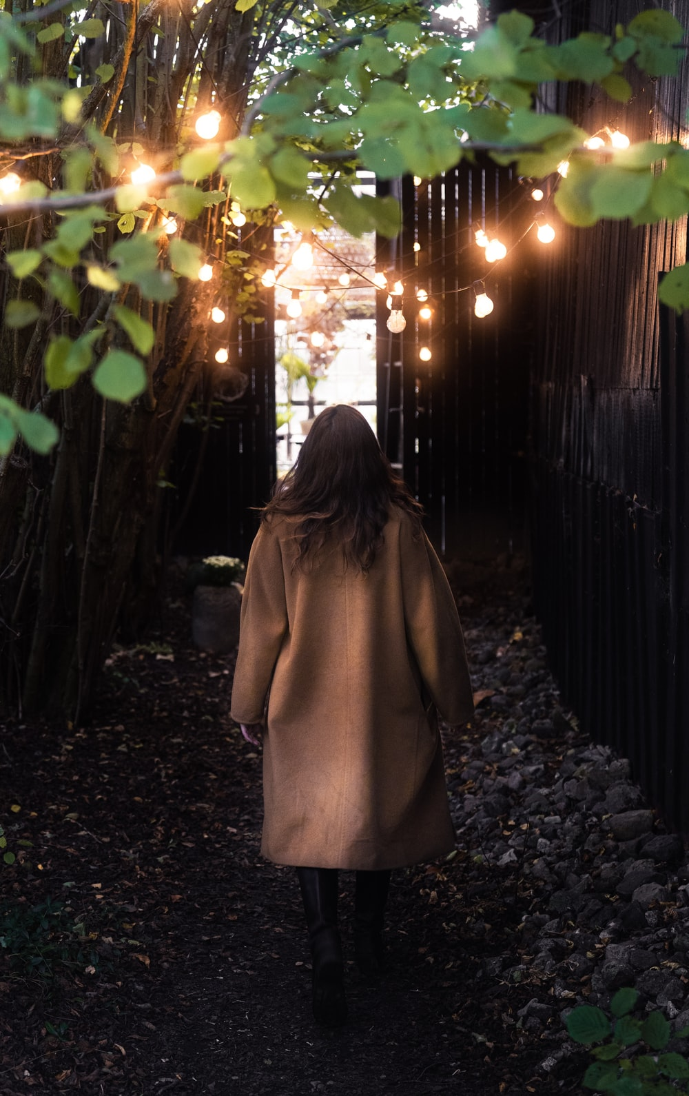woman in brown coat standing near brown wooden fence during night time