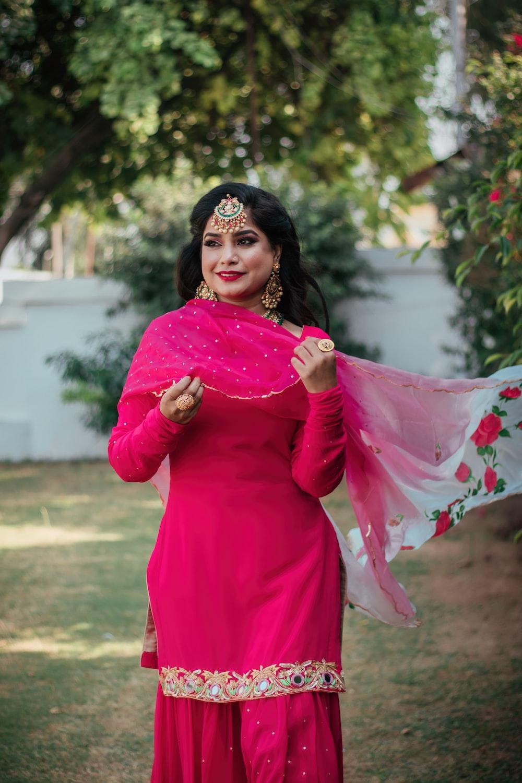 woman in pink long sleeve dress wearing black hijab