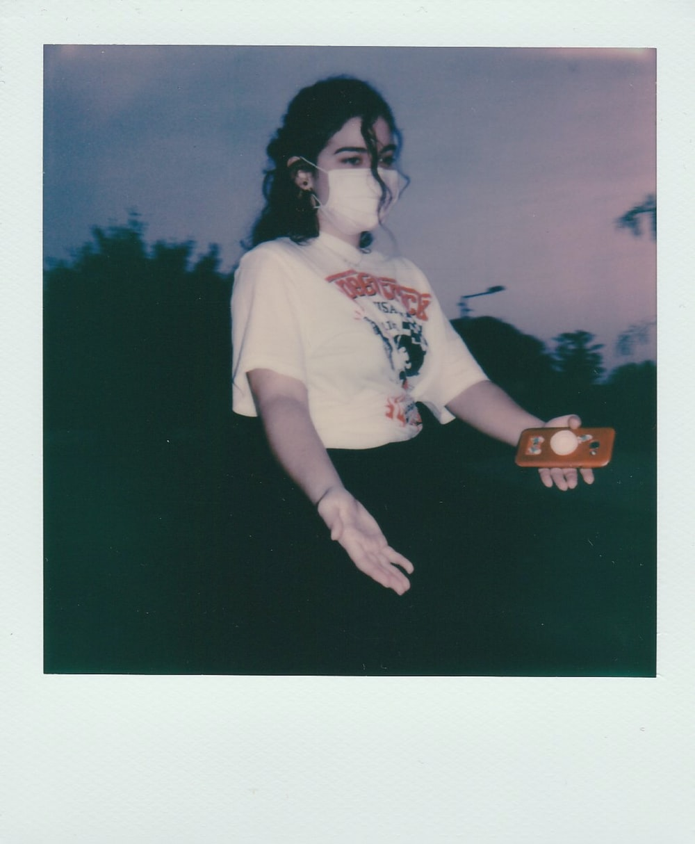 woman in white t-shirt holding brown wooden cup