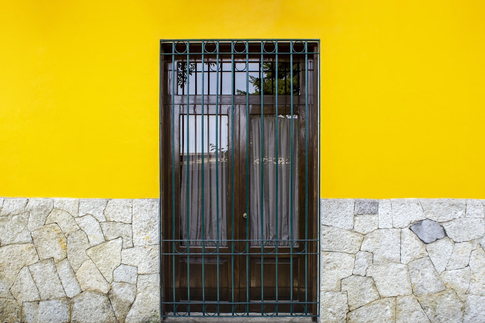 grey metal door on yellow painted wall