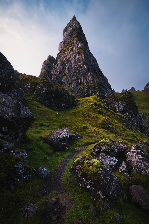 green grass field near rocky mountain during daytime