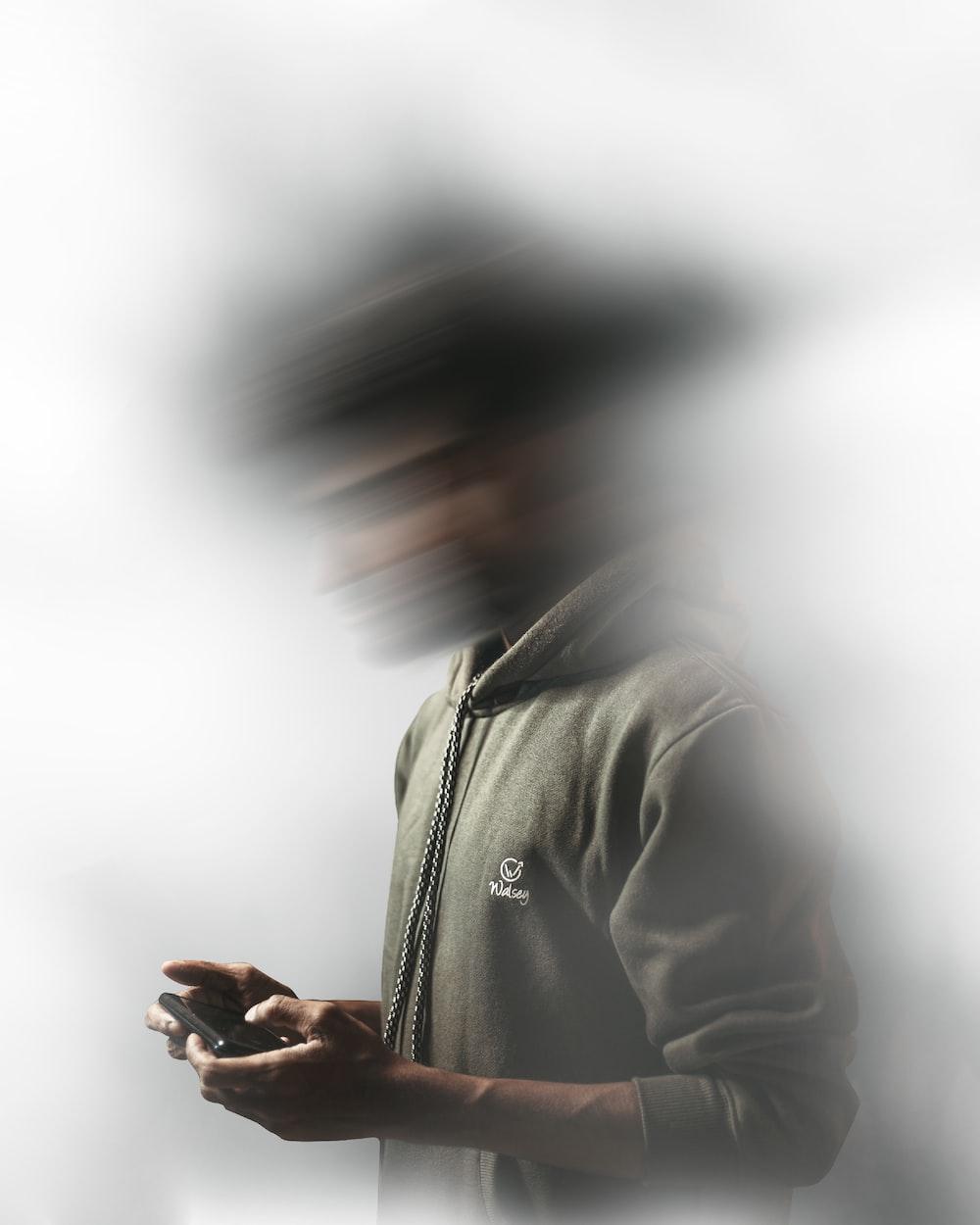 man in gray hoodie using smartphone