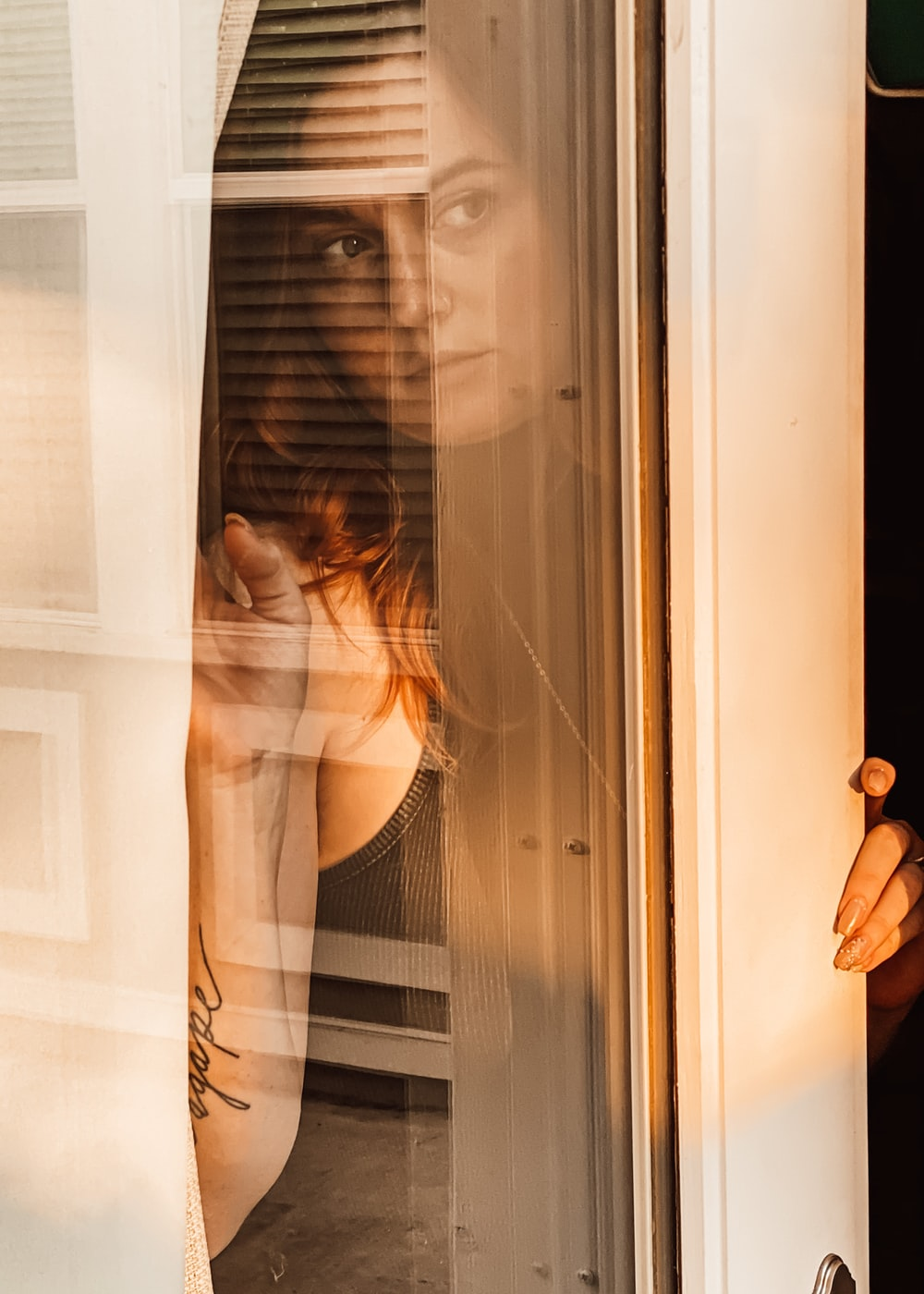 woman in white tank top standing beside white wooden framed glass window