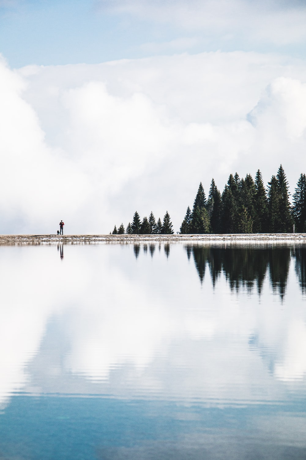 person standing on dock near lake during daytime