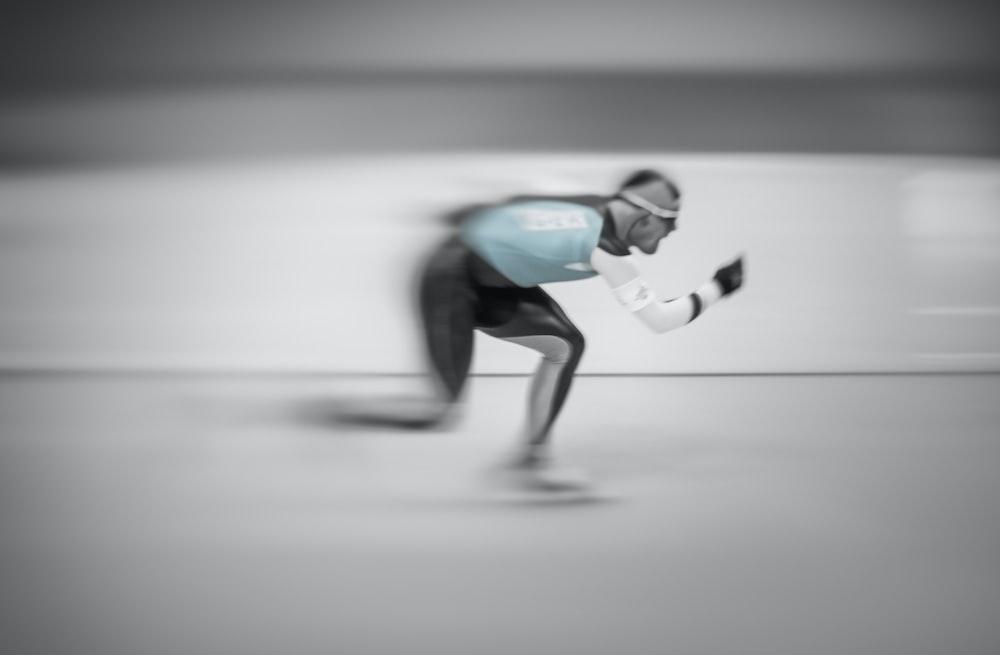 man in blue shirt and black pants doing skateboard stunts