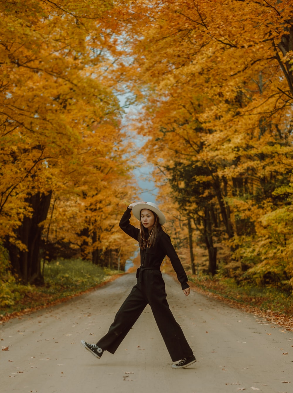 woman in black jacket and black pants walking on road between trees during daytime