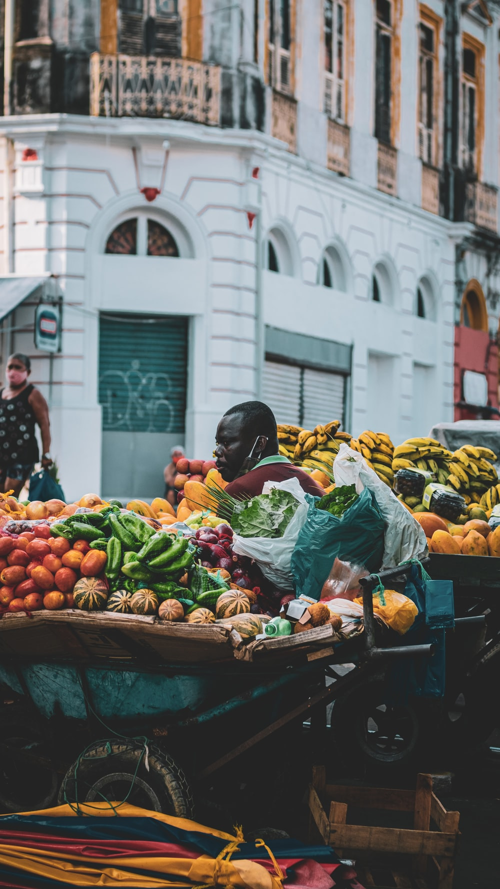 woman in black jacket holding green vegetable