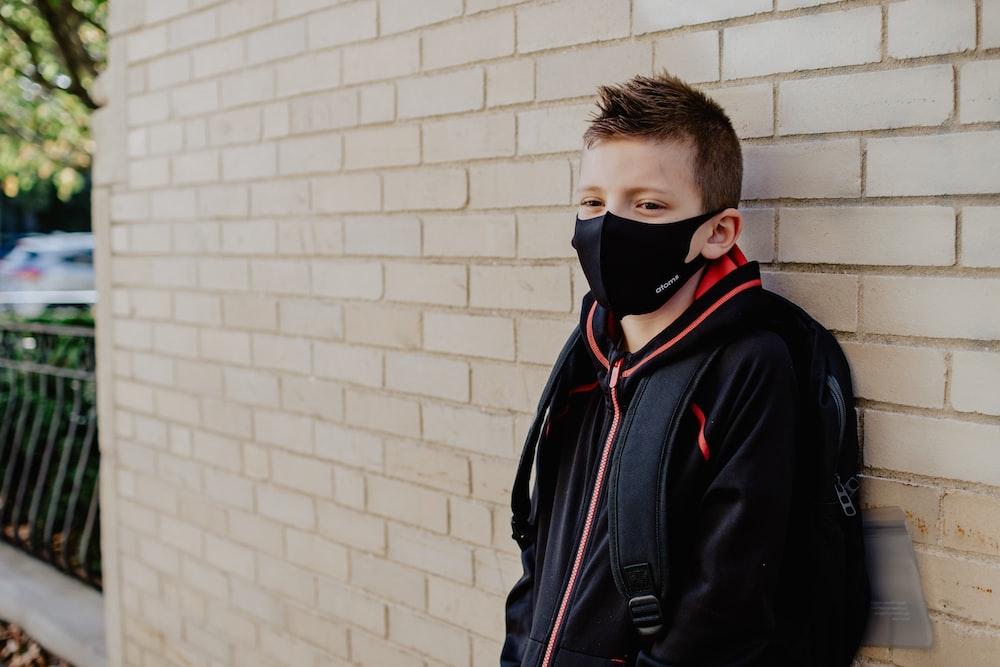 man in black jacket wearing white mask