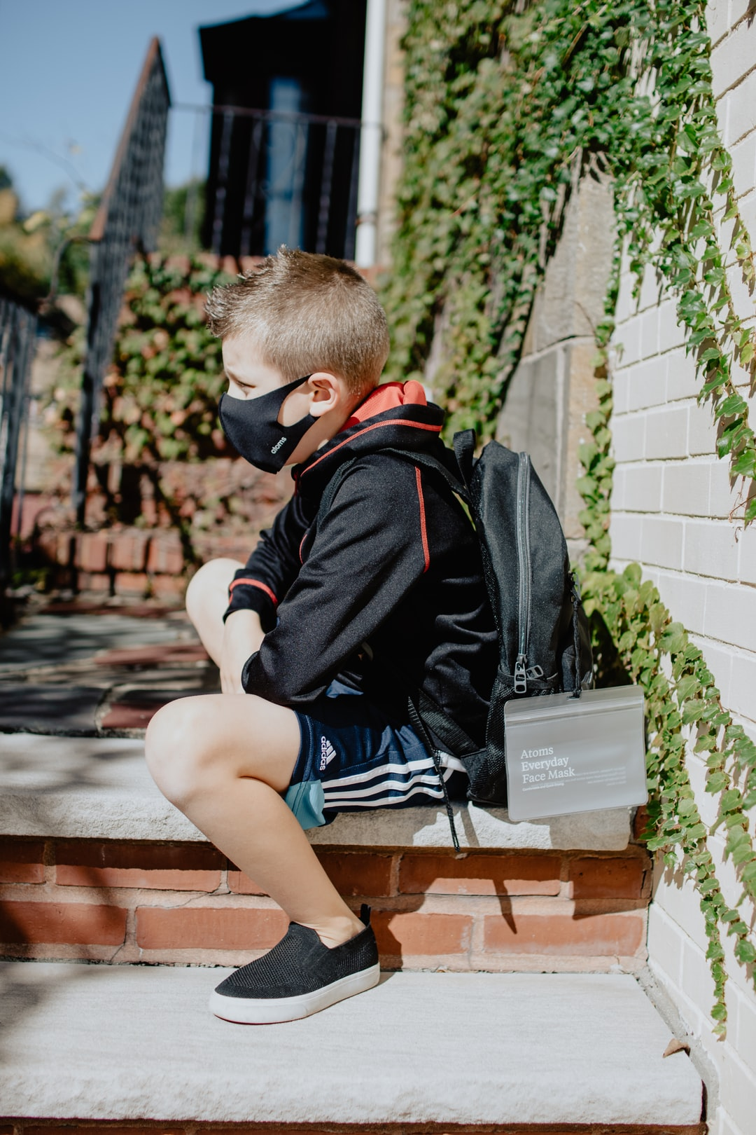 Boy sitting on a step with a mask on
