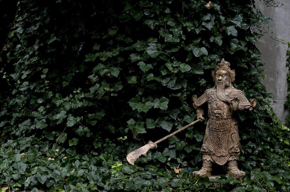 brown concrete statue near green leaves