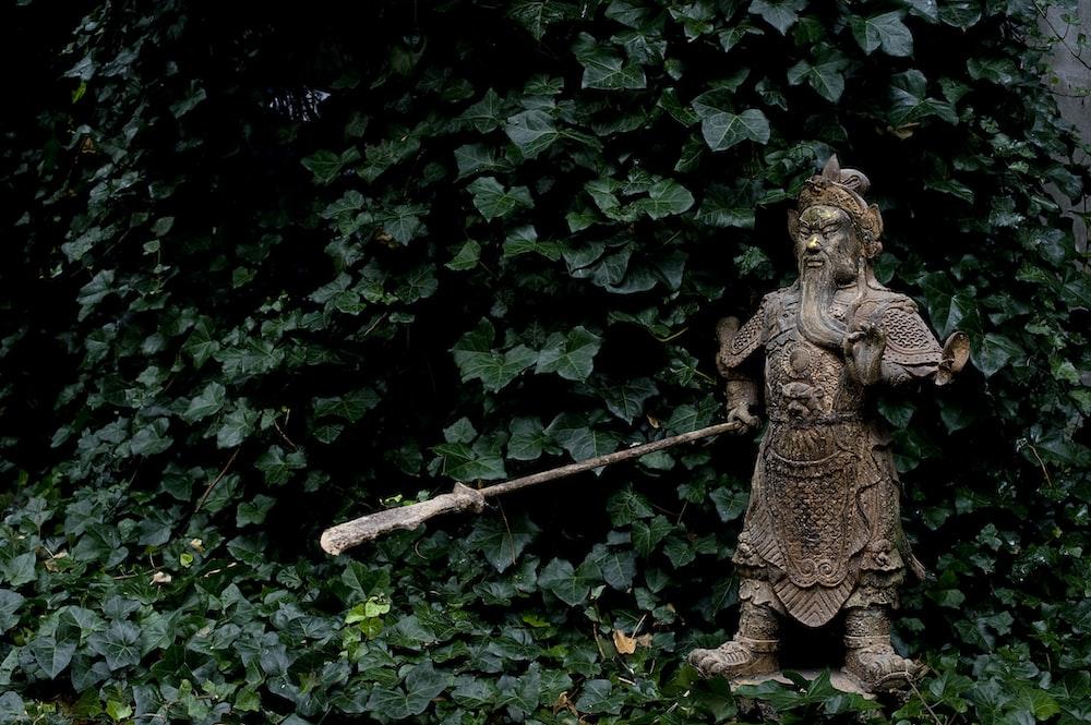 brown ceramic angel figurine on green leaves