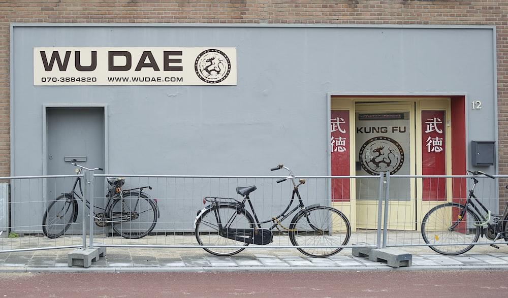black city bike parked beside white wall