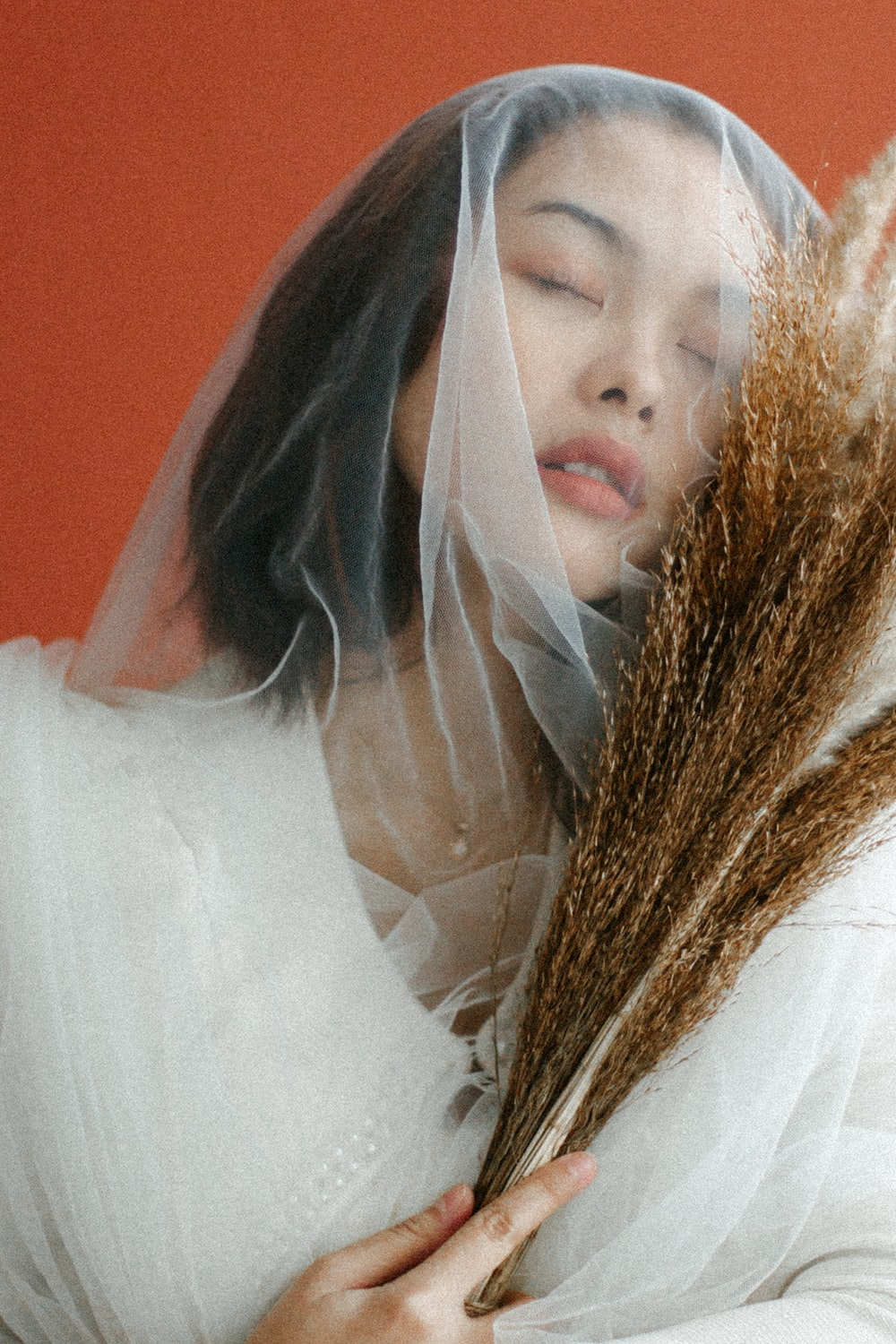 woman in white dress covering face with white textile
