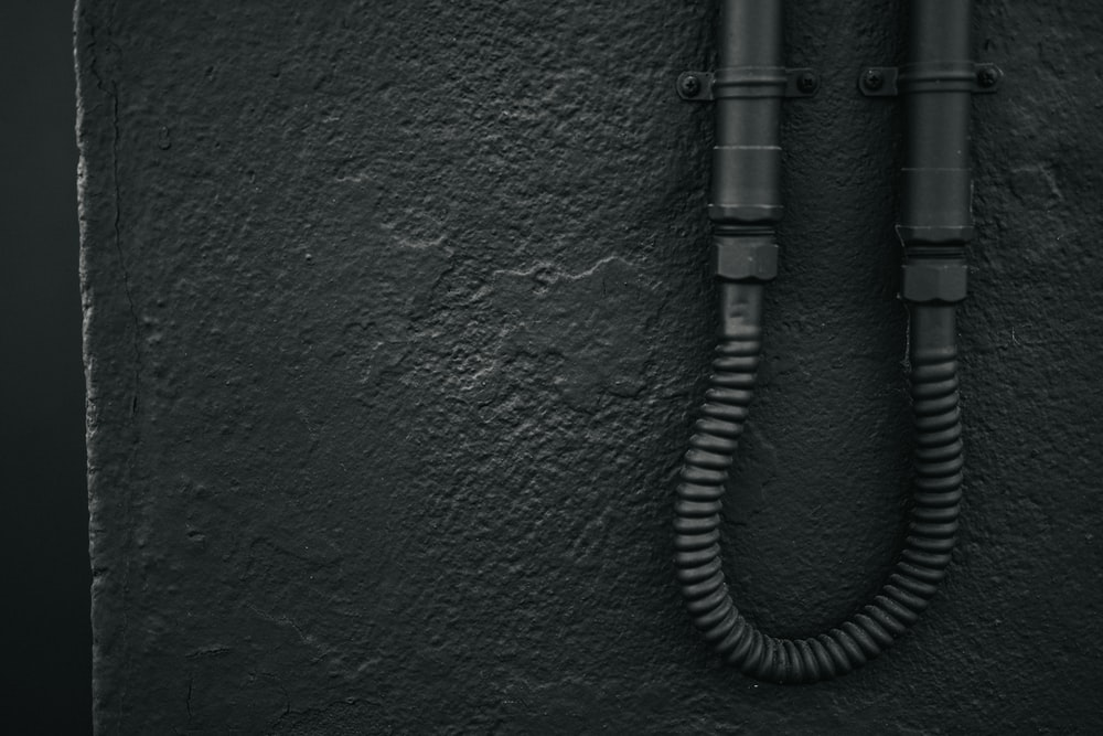 black coated wire on green concrete wall