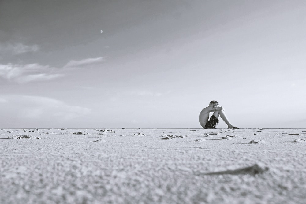 grayscale photo of man sitting on sand