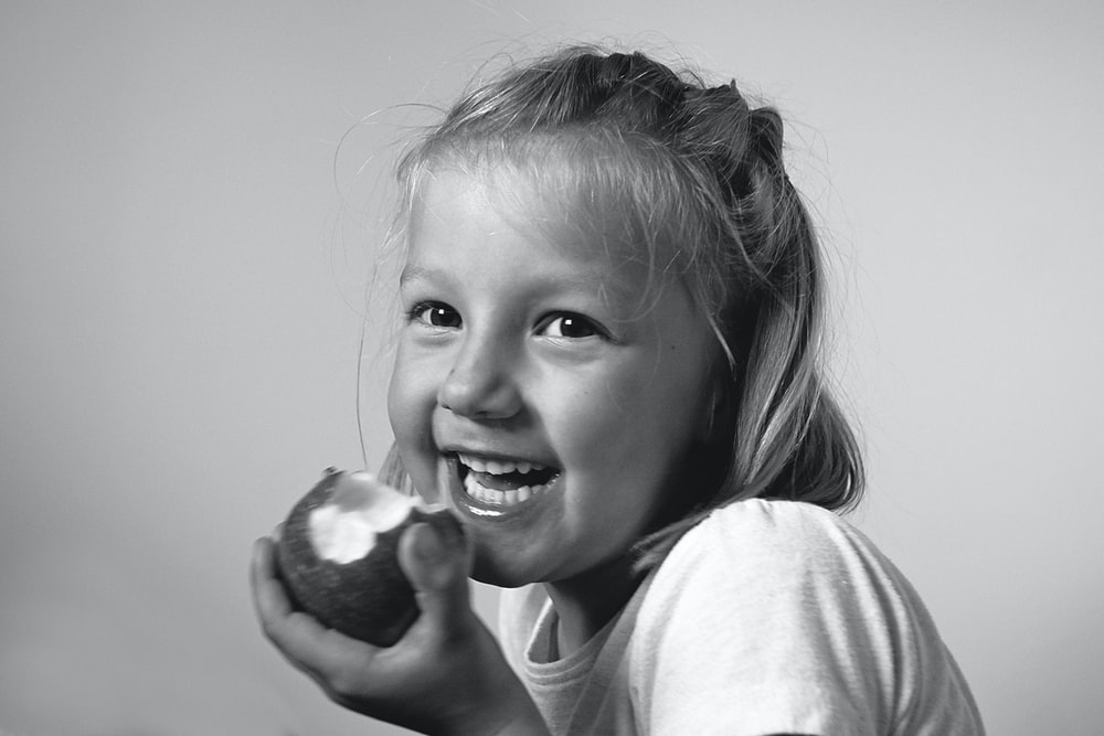 grayscale photo of girl holding round fruit