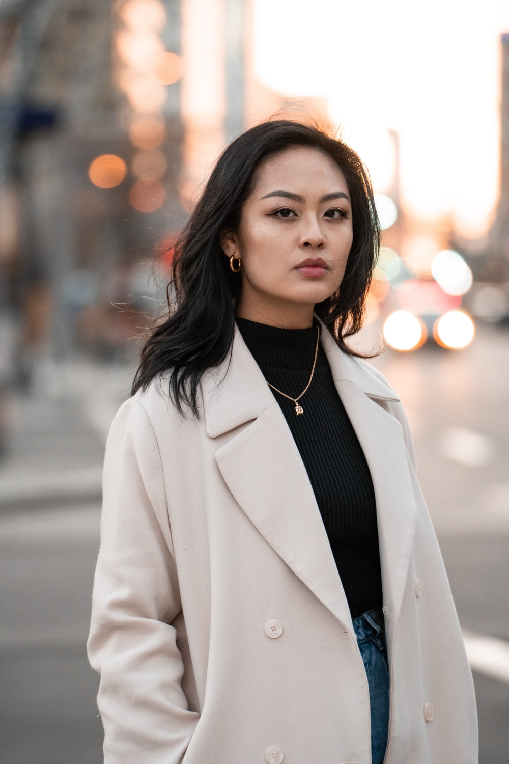 woman in white blazer standing on road during daytime