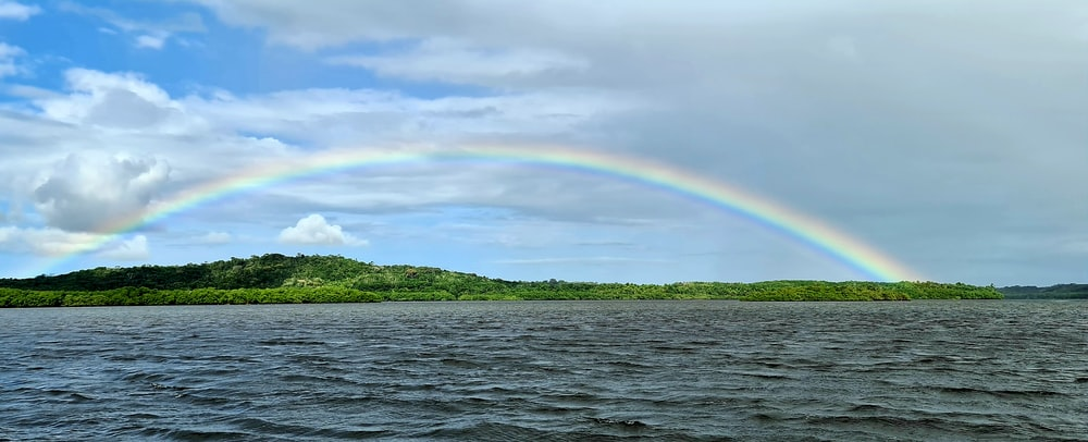 rainbow over green mountain and body of water