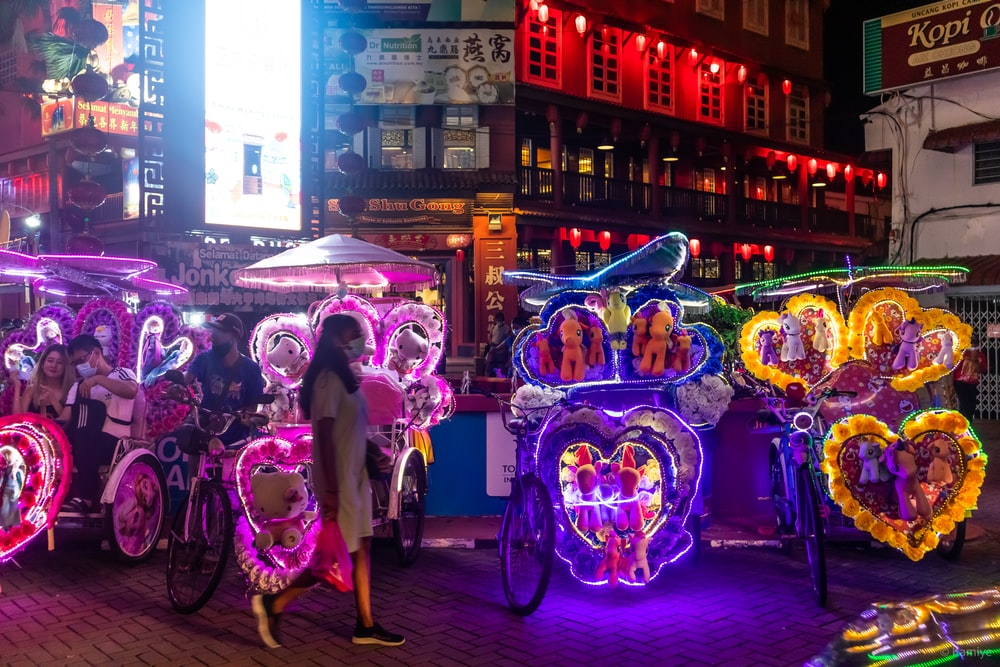 people walking on street with balloons during night time
