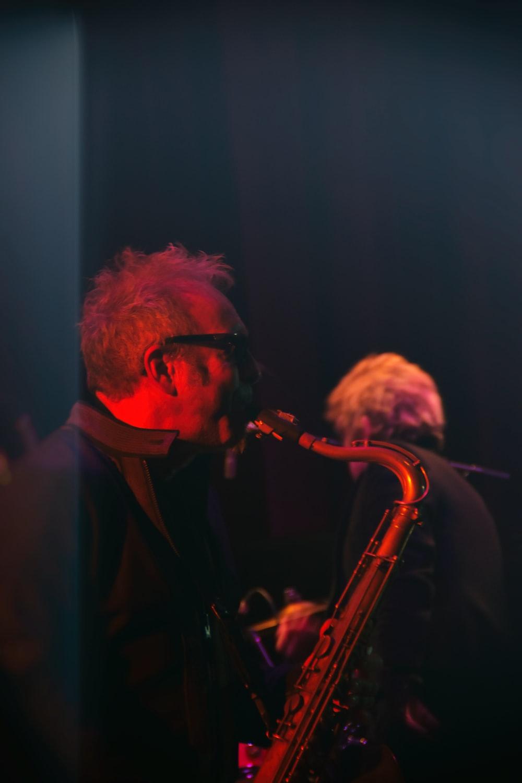 man in black suit playing saxophone