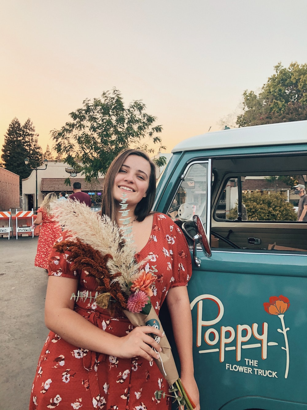 woman in red and white floral dress leaning on blue car