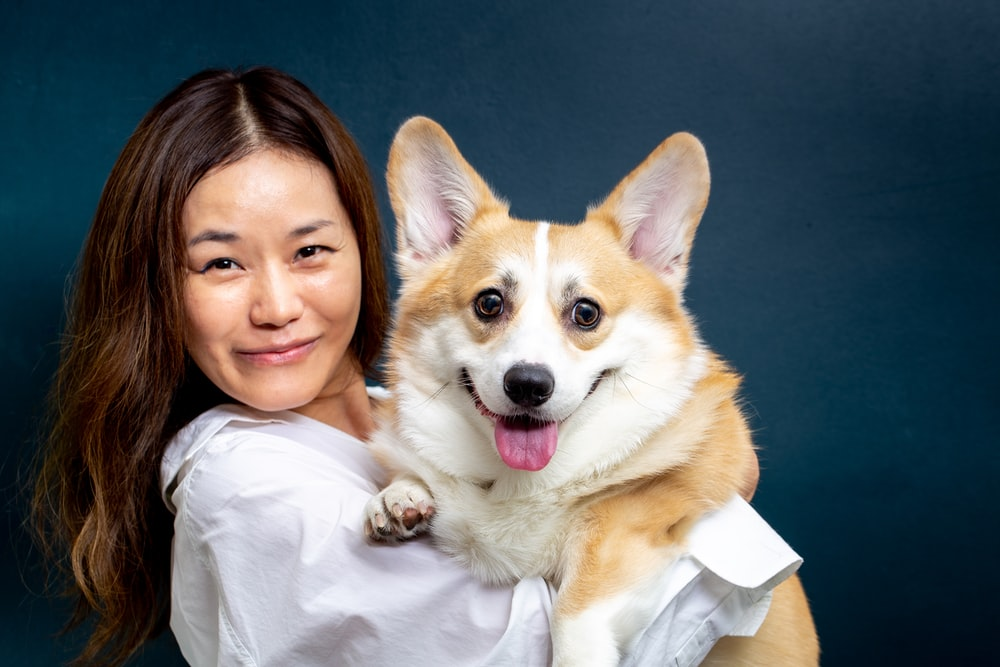 woman in white shirt holding brown and white dog