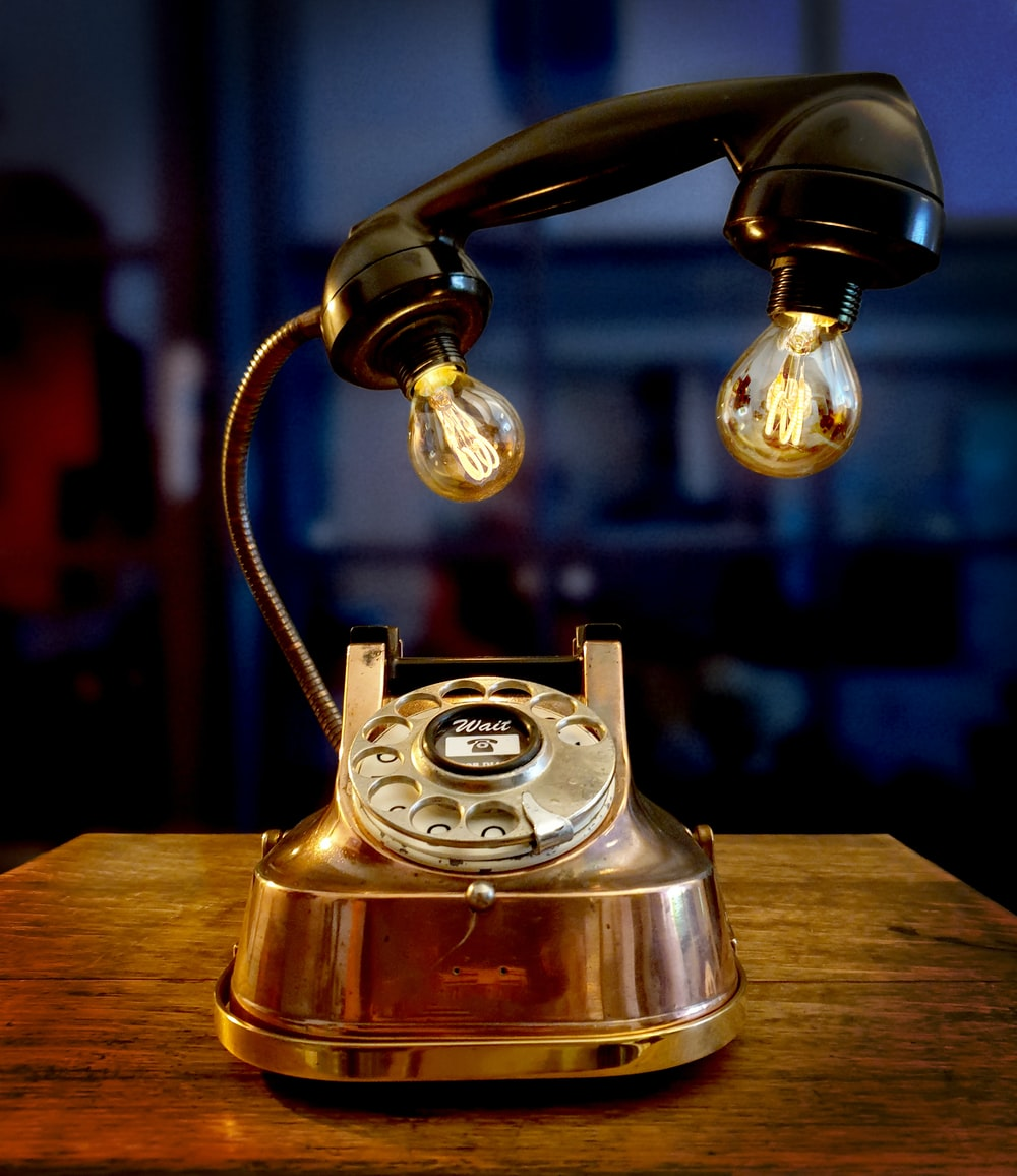 gold rotary phone on brown wooden table