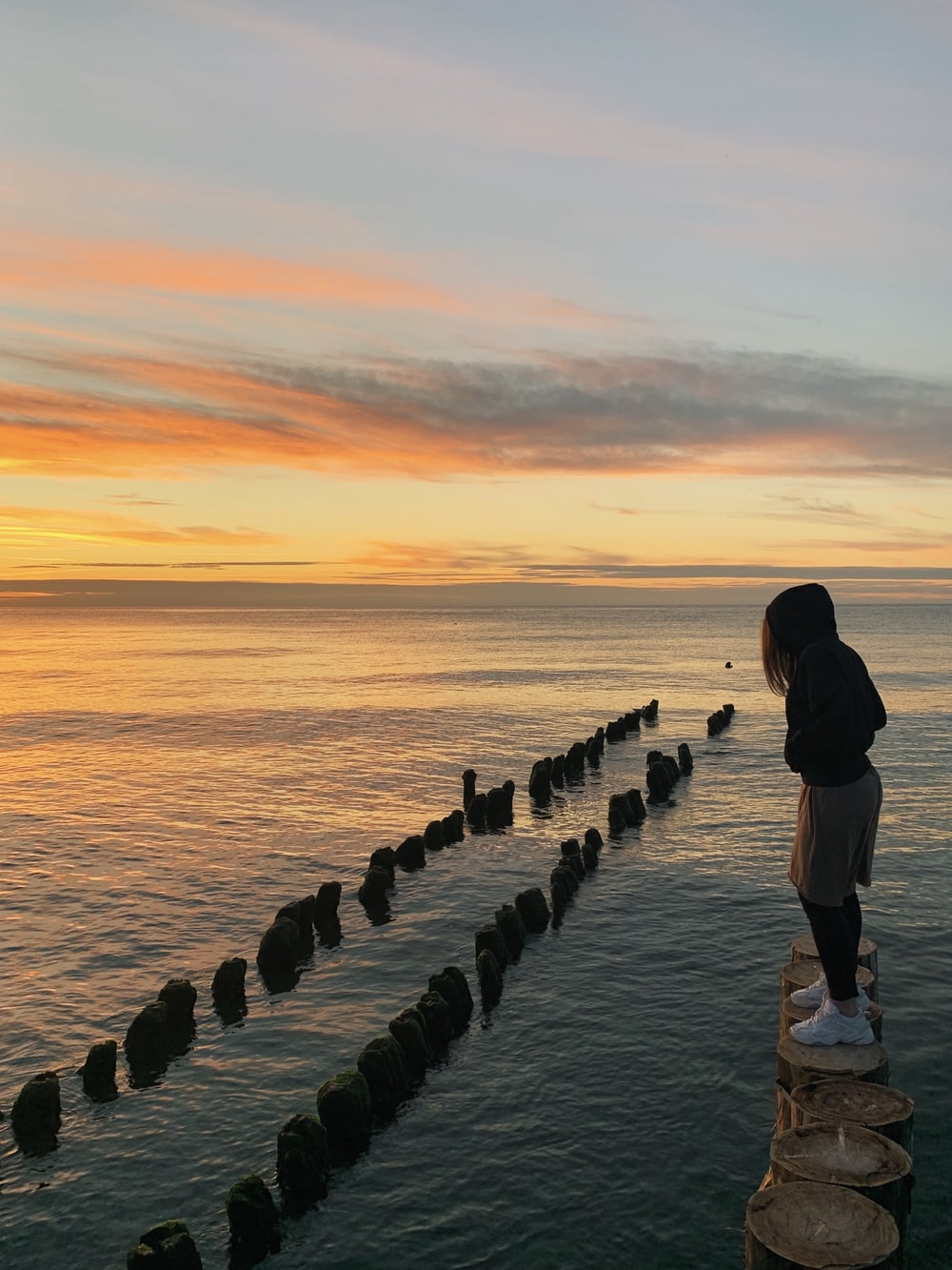man in black jacket standing on gray concrete dock during sunset