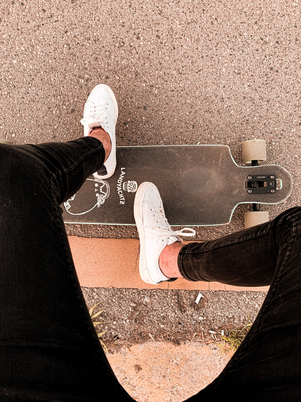 person in black pants and white sneakers