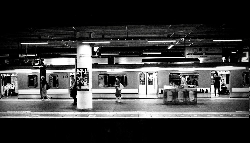 grayscale photo of people in train station