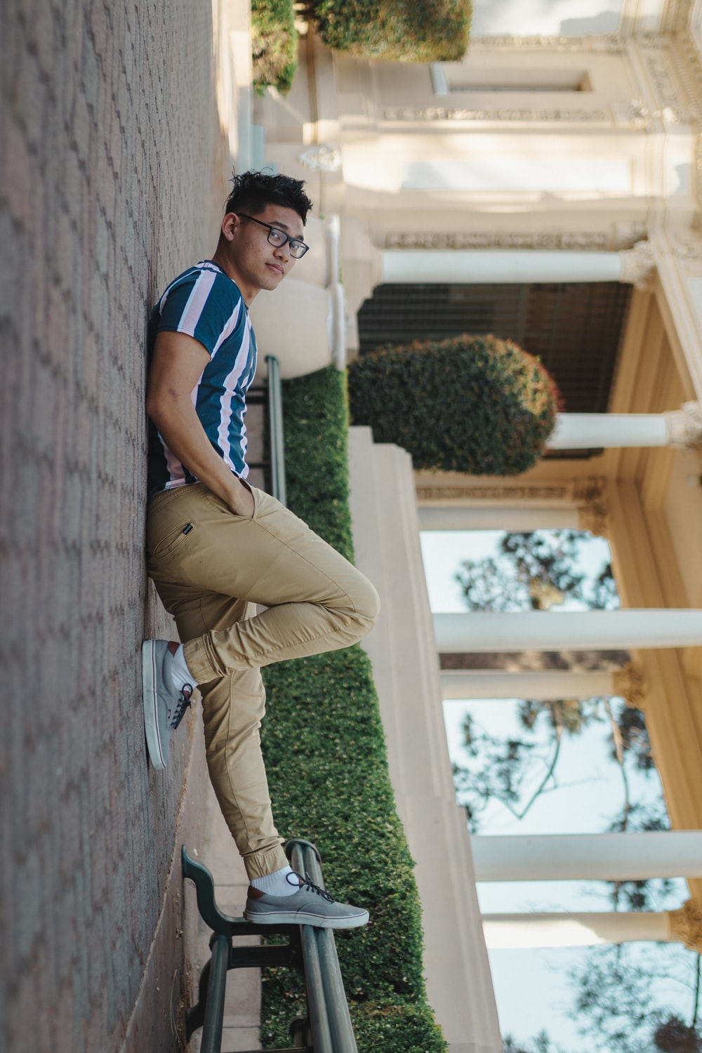 man in blue and white stripe polo shirt and brown pants sitting on brown wooden fence