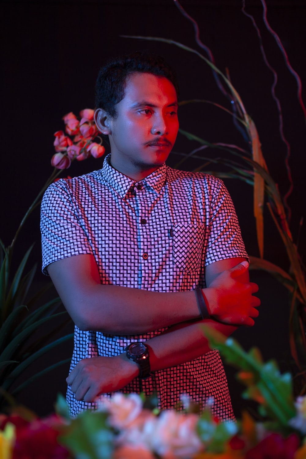 man in blue and white checkered button up shirt standing near red flowers