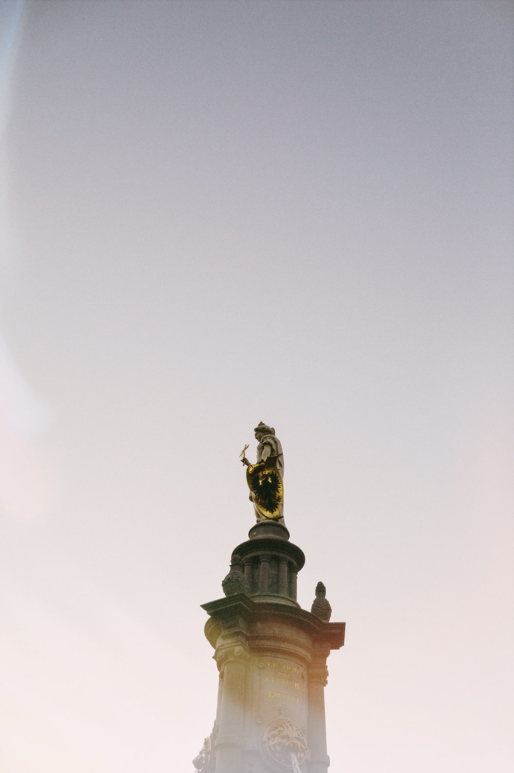 gold statue under white sky during daytime