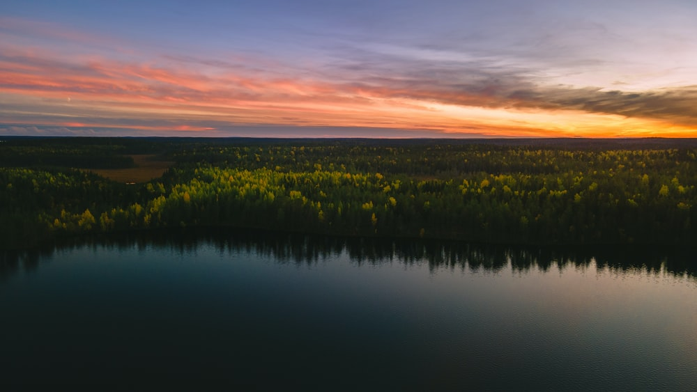 green grass field near lake during sunset