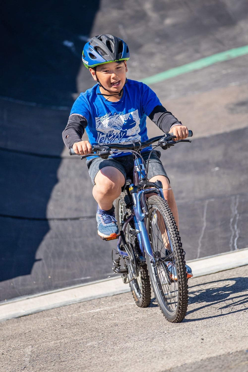 boy in blue long sleeve shirt riding on bicycle