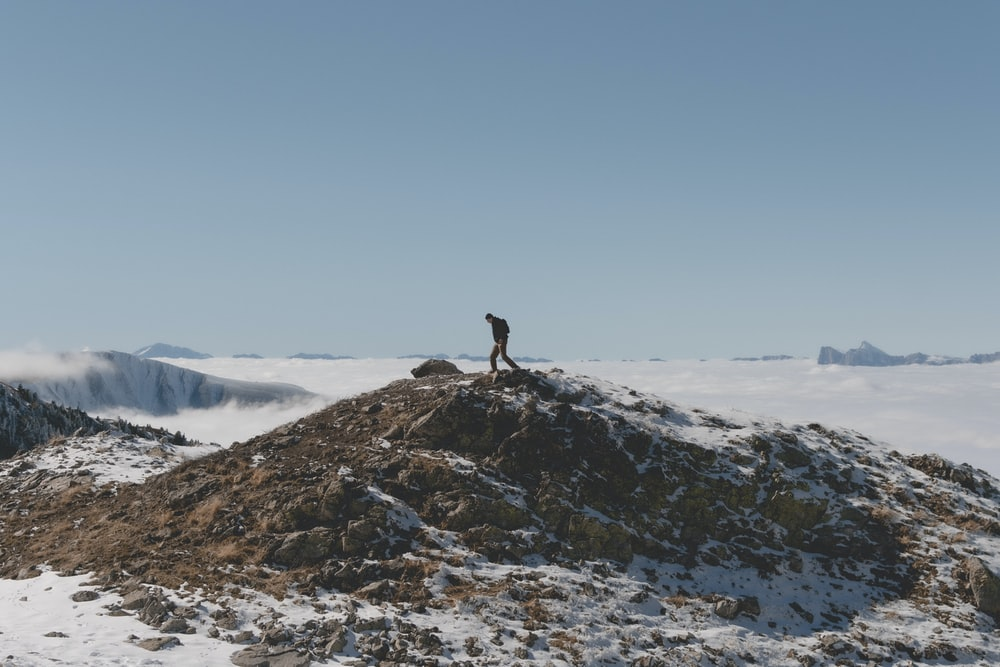 person standing on rock formation covered with snow during daytime