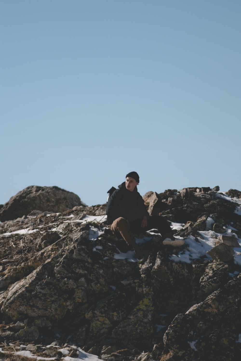 man and woman sitting on rocky mountain during daytime
